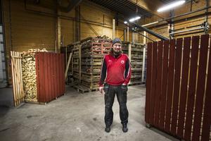 Tommy Björklund är mannen bakom Hyr en vedbod-konceptet. Bakom honom står en vedbod utan tak som är fylld med ved.