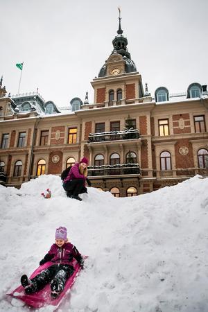 Isabelle Forslund och hennes mamma Gabriella åker madrass i snöhögen på torget.