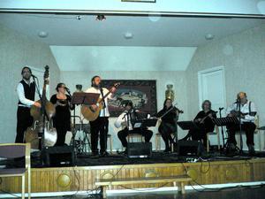 Från vänster ser vi Örjan Herman Schweiler, ståbas, Maja Kihl, sång o rytm, Putte Kihl, gitarr, Kjell Landberg, dragspel, Sara Li Söderberg, fiol, Lena Eriksson, mandolin och Per Schultz, gitarr.