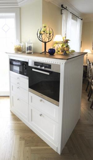I stället för att bygga en stapel i köket med ugn, mikro och förvaringsutrymmen har de byggt en skänk. Det ger ljus och luft.