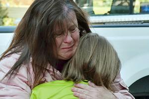 En förälder kramar sitt barn utanför skolan i Newtown, Connecticut.