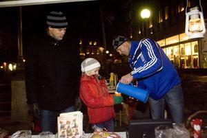 Peter Forsström får hjälp av Klara och Pär Larsson när han häller upp en mugg glögg. De ser till att dra in pengar till Hudik Gympans verksamhet.
