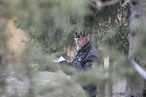 Polis ute i skogen ser till att avspärrningarna respekteras.