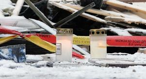 Två ljus brinner vid den lägenhet där en person omkom i samband med helgens brand.