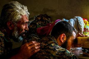 Två av syriska militärrådets soldater, MFS, spanar efter IS från sitt fäste i Hasakah i Syrien.