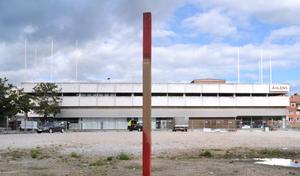 Utsättningspinnen visar hur stor yta av torget (till höger) som tas i anspråk för den nya byggnaden.