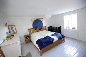 Sovrummet är inrett i New England-stil med liggande plank på väggarna och lackat trägolv.