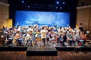 Dirigenten Rune Hannisdal från Bergen instruerar blåsorkester hur musiken ska gå.