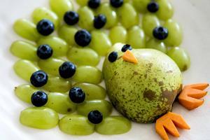 En påfågel gjord av vindruvor, blåbär, päron och morötter blir ett perfekt mellanmål för både stor och liten.