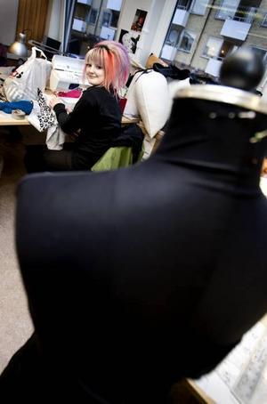 Sömnad. Sophia Nordström sitter och syr ett linne i leopardmönstrad trikå.