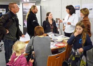 Hilje Blaauw, i vit skjorta, på en flyttmässa i Holland i samspråk med landsmän som är intresserade av hur det är att bo och leva i Sverige.