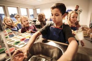 Benjamin Andersson, 7 år, rengör vattenfärger efter att ha målat på temat