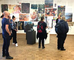 Konstnären och läraren Bo Ljung (närmast målningarna) berättar om årets utställning av Västerås Konstskola på Konstmuseet.