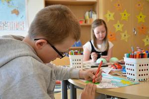 Rasmus Abrahamsson koncentrerar sig på sitt målande. I bakgrunden målar Ellen Dahlström ett påskägg.