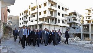 Syriens president Bashar al-Assad, i mitten, vid ett framträdande i Daraya under måndagen, på en bild som släppts från den syriska nyhetsbyrån Sana.