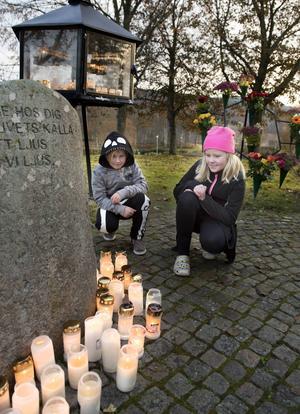 Agnes och Emma Andersson tänder ljus vid Selångers kyrkogård för bekanta som gått bort i cancer och för pappas farmor Hilma.