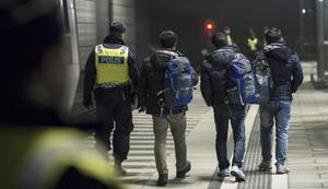 Polis eskorterar asylsökande från ett tåg som stannat vid Hyllie station utanför Malmö.