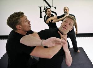 """Mot mattan. Thaiboxaren Rickard Nordstrand tränar grepp med Mikael Persbrandt. I bakgrunden Olivier Sa och Joseph Beddelem, stuntmän som jobbat med filmer som Bourne-trilogin och """"Inception""""."""