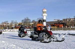 Människor kör skoter på Storsjöns is en solig vinterdag.