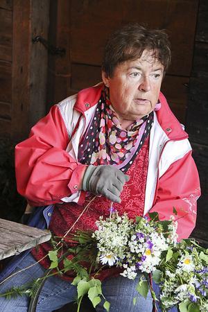Ursula Lindblom band också kransar. Himlen har öppnat sig, konstaterade hon när hon tittade ut på gårdstunet där stora vattenpussar hade bildats.