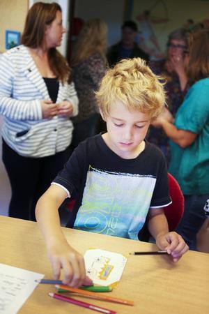 Dante Fladval ritar en bil på sin skylt som ska fästas på korgen vid klädhängarna i korridoren.