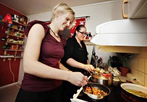FÖRSÖKER HJÄLPA. Arbetarbladets reporter Marika Johansson får förtroendet att smörsteka kantarellerna. Värdinnan Matilda Göthlund visar med van hand hur man gör älgfärsbiffar                                                  med bacon.
