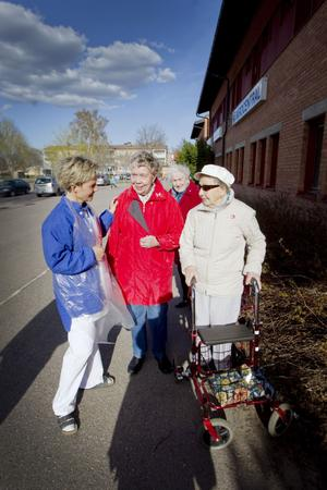 Verksamhetschef Ewa Hammarin hälsar på Gerd Hedström, Greta Eriksson och Irma Andersson.