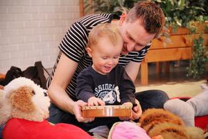 Erik Nymans får slå på tamburinen och är mycket nöjd över det. Pappa Jonas hjälper till.