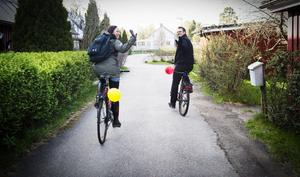 Klockan 18:49. Karin och Kalle cyklar vidare mot Björktjära. Ballongerna symboliserar deltagandet i tävlingen.