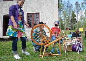 Idag är det inte många som kan spinna. Ann Andersson visar Adrian Delhag hur han ska göra. Farmor tittar på. Foto: Maria Andréasson
