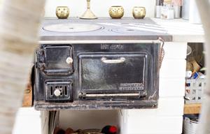 Den gamla vedspisen värmer både rummet och maten.