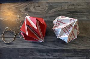 De diamantformade juldekorationerna har Linnéa gjort av vanlig rött papper. På den högra har hon limmat fast mönstrat julklappspapper.