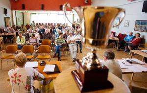 """Ståtligt uppställd för alla tävlande och åhörares beskådan stod segerbucklan från förra årets riksfinal av """"Vi i 65:an"""", som PRO Oden kammade hem."""