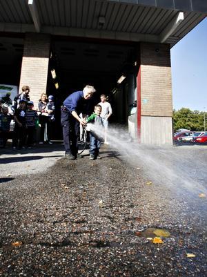 Elton Åkerblom, 4, fick hjälp av Posa Serenius att rikta brandslangen.