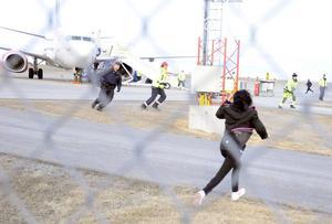 Tumult uppstod på flygplatsen och pojken skadade en bil när han försökte komma fram till sin avsvimmade mamma.