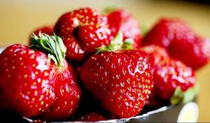 Dela jordgubbarna på hälften och tryck ner dem i fyllningen.