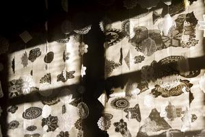 Anneli har gjort en snöflingeliknande fond av gamla virkade dukar som hon köpt på loppisar och fäst vid långa snören från taket.
