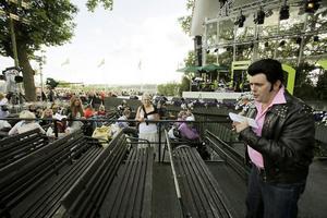 Toralf Nilsson i färd med att skriva autografer i publikens allsångshäften.