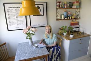 Köket är original även om luckorna blivit omlackerade. Bordet med perstorpsplatta passar perfekt till husets ålder, och vasen på bordet är ett av Karolines senaste loppisfynd.