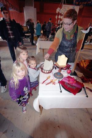 Vackert dukade bord intresserade både barn och vuxna. Helena Hagström förevisar ett inslag i utställningen slöjden och maten. Närmast i bild står Ebba Olofsson och syskonen Nindra och Meja Almén Sundqvist.
