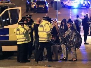 Räddningspersonal hjälper chockade konsertbesökare efter terrorattentatet i Manchester.