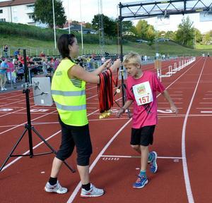10-årige Bosse Lövgren från Falun får segermedalj i Kidsenloppet.
