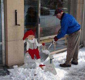 Tage Norgren lägger upp snö runt tomten som nu sprider lite julglädje utanför kommunhuset.