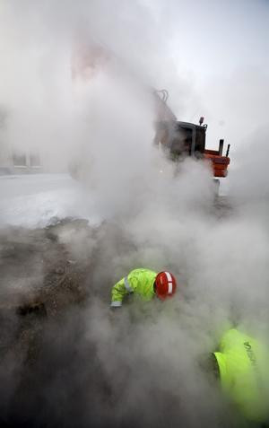 Fredrik Karlsson i röd hjälm och Kjell Karlsson fick jobba i ångan från det heta fjärrvärmevattnet som fyllde gropen när den läckande ledningen grävdes fram för att repareras. Några timmar senare var läckan igensvetsad och värmen kunde släppas på igen.
