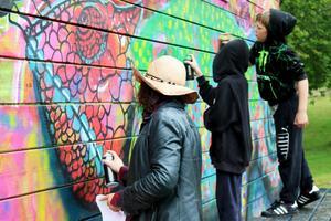 Kreativa trion Charlie Granberg, Arvid Hedlund och Allan Nordström lät inte regnet hindra måleriet. Foto: Pia Enocson
