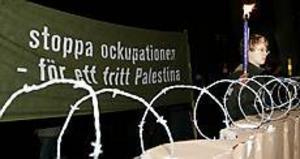 Bakom en symbolisk mur av lastpallar på högkant står Patrik Hertzman somtillhör Ung vänster. � Jag är här för att visa motstånd mot muren som Israel håller på att bygga. Den visar på ett konkret sätt vilken politik Israel för, säger han. Foto: LASSE HALVARSSON