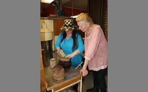 Gunilla och Karin demonstrerar hattstockarna som fortfarande används.FOTO: KERSTIN ERIKSSON