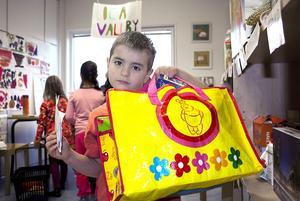 """""""Jag ska köpa juice, jordgubbar, våfflor och popcorn"""", säger Filip Haddad och visar upp sin matkasse i den mataffär som barnen har byggt upp."""