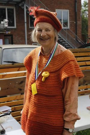 Karin Gerstel, 79 år, bär mössa, tröja och sidenskjorta, alla färgade med svamp och både tröjan och mössan är konstruerade med den traditionella nålbindningstekniken.