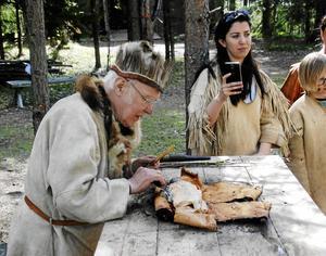 Jägare Mård, (Curt Lofterud) delar ut röding tillagad i en kokgrop.